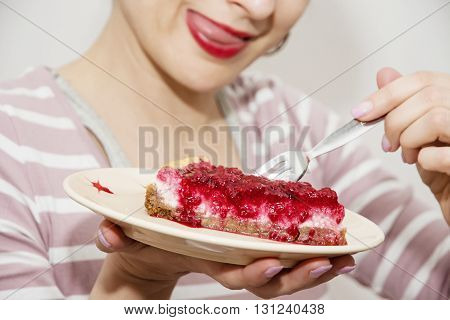 Beautiful positive caucasian woman is tasting a piece of cheesecake with raspberries. Sweet food theme. Joyful woman. Cherry lips. Vibrant colors. Sexy woman. Food theme. Gourmand woman.