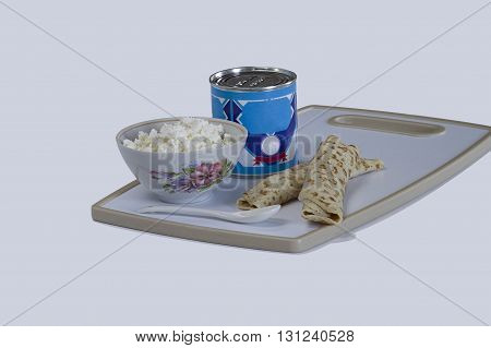 pancakes with cottage cheese and a can of condensed milk on a tray