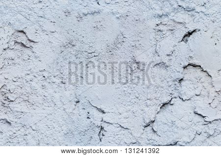 Texture of a blue painted plaster wall with cracks