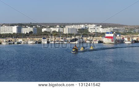 CYPRUS, AYIA NAPA - SEPTEMBER 3, 2015: View of moored boats and fishing boats in the bay of Ayia Napa. In the distant visible Hotels