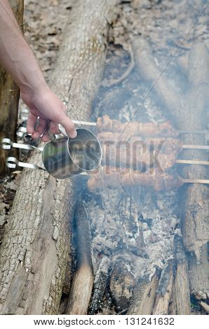 hot pork meat on metal skewers roasted on coal outdoors. Grilling shashlik during picnic outdoors.
