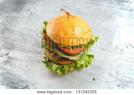 Big beef steak burger with vegetables and herbs on rustic wooden background horizontal top view