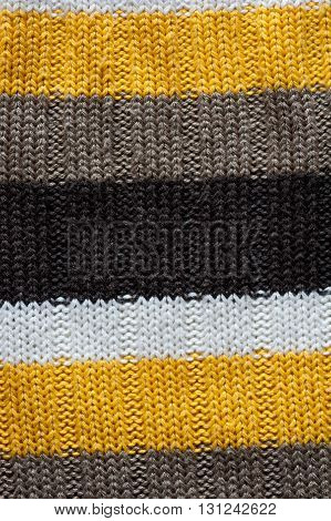 A close up of a wool knitted background with black, yellow and brown