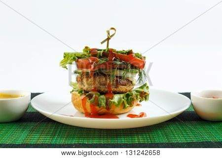 Big beef steak burger with vegetables and herbs on white plate on green bamboo placemat against white background horizontal view close up