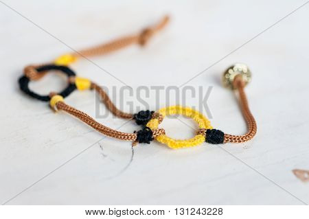 Close up of a crochet bracelet with black, yellow and brown