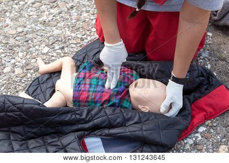 First aid training. Paramedic demonstrate Cardiopulmonary resuscitation (CPR) on infant CPR dummy. Child CPR dummy cardiac massage.