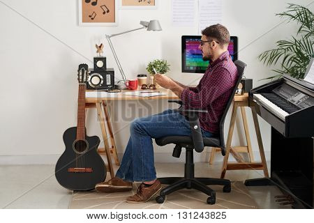 Side view of composer searching for ideas on internet