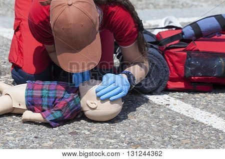 First aid. Paramedic demonstrate cardiopulmonary resuscitation - CPR on the infant CPR dummy.