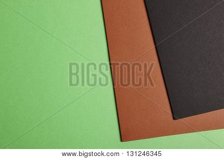 Colored cardboards background in green brown black tone. Copy space. Horizontal