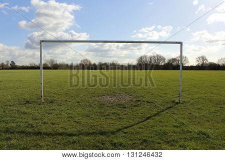 Goal Posts On A Field In The Sun With Blue Sky And Clouds