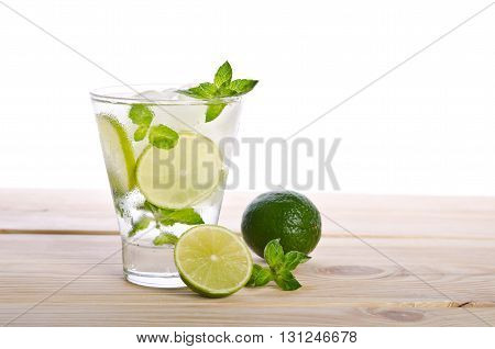 Mohito mojito drink with ice mint and lime on wooden table