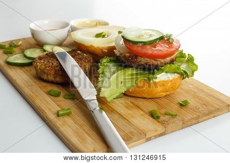 Cooking process of a sandwich burger ingredients on wooden cutting board on wooden table against white background fresh vegetables herbs fried meat buns sauces and knife horizontal view shallow DOF
