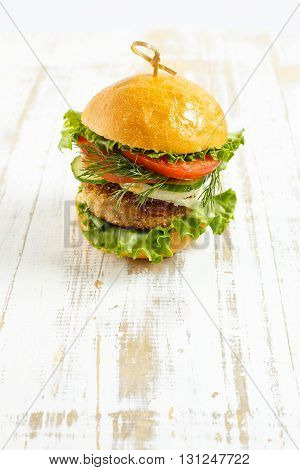 Big beef steak burger with vegetables and herbs on rustic wooden background close up