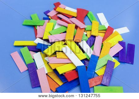 Do-it-yourself educational wooden colorful sticks made for stacking arranging and building. Learning through experience concept creative toy playing and educational approach concept.