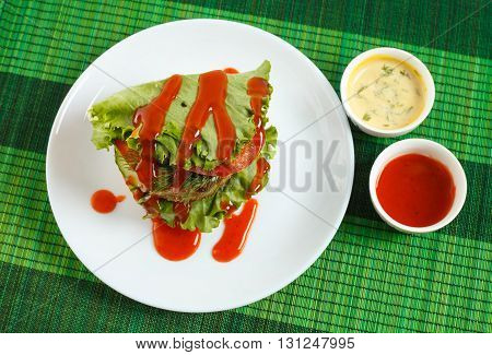 Big beef steak burger with vegetables and herbs and sauces on green bamboo placemat horizontal top view