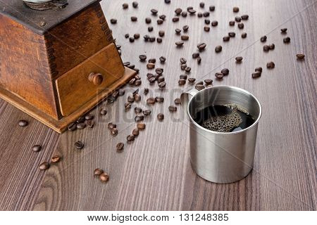 Metallic cup of coffee old wooden grinder on the left and beans on the table
