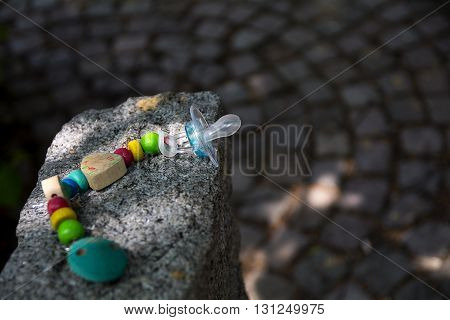 baby pacifier with a chain made of wooden elements left on a granite stone at the playground selected focus narrow depth of field