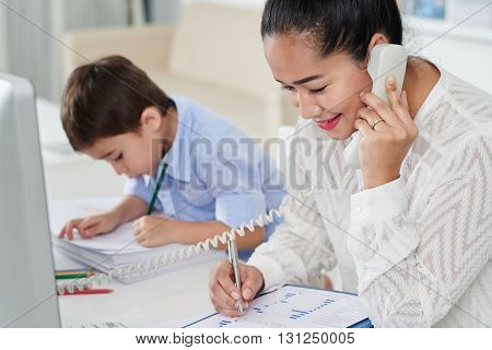 Female financial advicer consulting client on phone when her kid drawing on important document