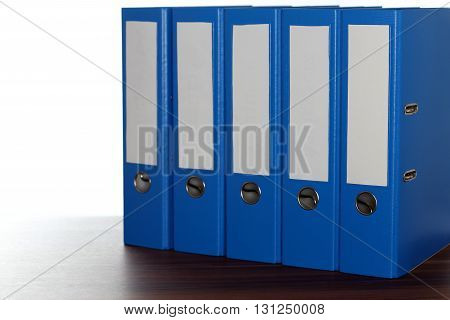 five file folders in a row on a desk