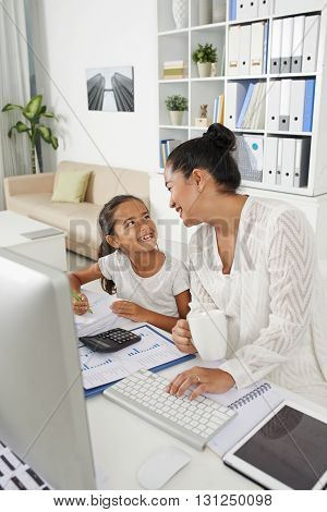 Business woman chatting to her daughter when having coffee break