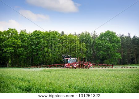 old red tractor spraying fertilizer or herbicide on a field near the forest