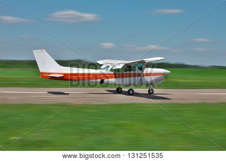 Light private plane is taking off from the airfield