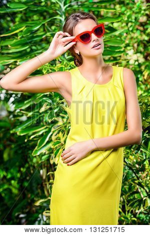 Stylish young woman in bright yellow dress and pin-up glasses enjoying summer. Beauty, fashion.