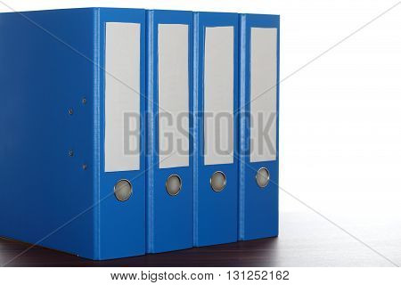 four file folders in a row on a desk