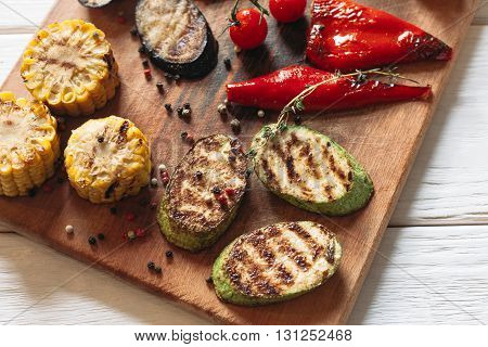 Delicious grilled vegetables on cutting board. Flat lay of close-up corn, pepper, vegetable marrow, eggplant on wooden background.