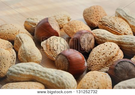 Almonds hazelnuts and peanuts scattered on a wooden board
