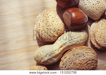 Almonds hazelnuts and peanuts on a wooden board background