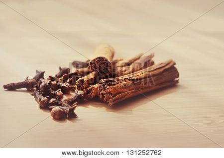 macro of clove spice cinnamon sticks on a wooden board