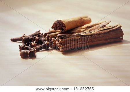 clove spice cinnamon sticks on a wooden board