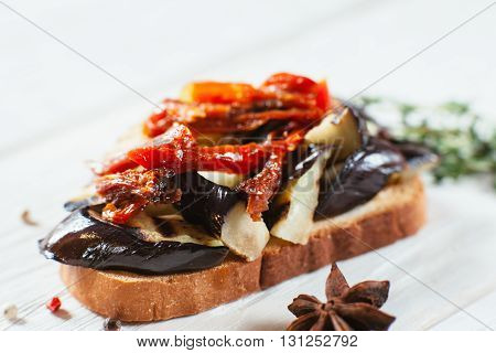 Eggplant sandwich with tomatoes on white wooden table. Close-up of eggplant bruschetta. Front view vegetarian vegetable dish