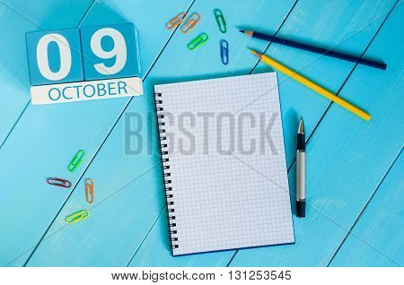 October 9th. Image of October 9 wooden color calendar on blue background. Autumn day. Empty space for text.