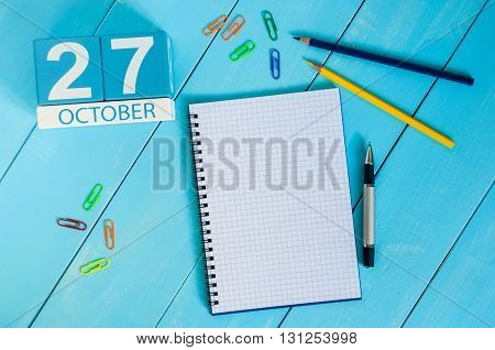 October 27th. Image of October 27 wooden color calendar on blue background. Autumn day. Empty space for text.