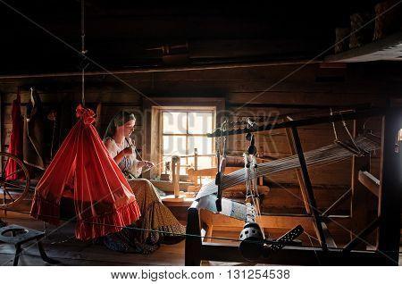 Women In Traditional Costume  Weaves On Kizhi Island, Karelia, Russia.