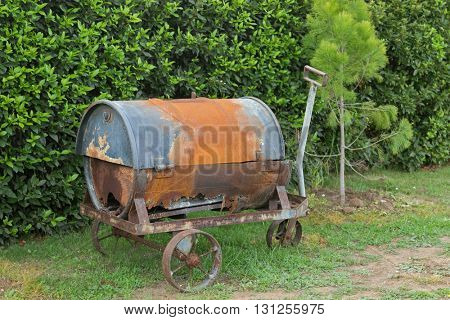Old and rusty metal wheelbarrow with old barrel on it, to decorate the garden