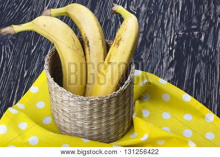 Bunch of bananas in the basket on wooden table.
