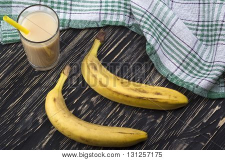 Banana juice with bananas on the wooden background