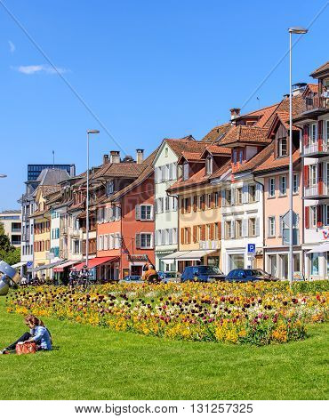 Zug, Switzerland - 6 May, 2016: people and buildings on Chamerstrasse street. The city of Zug is the capital of the Swiss canton of Zug.