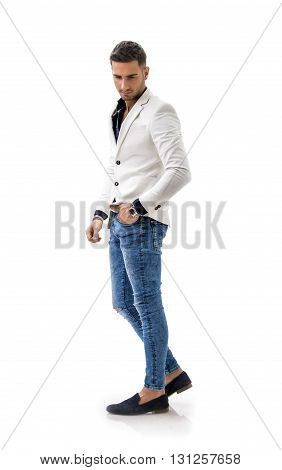 Handsome young man in blue shirt, white jacket and jeans posing isolated on white background in studio. Full length shot