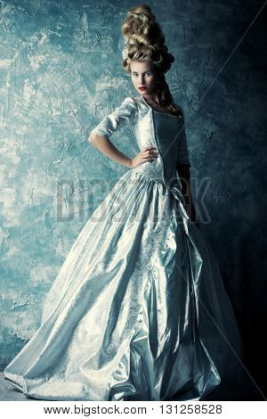 Fashion portrait of a beautiful woman in a luxurious medieval dress and high hairdo in vintage style. Baroque and Renaissance style. Historical dress, hairstyles history. Full length portrait.