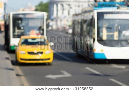unsharp photo closeup of the car of a yellow taxi and bus or trolleybus on the street city for industrial indistinct background