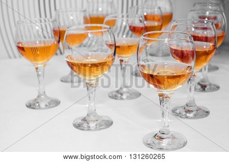 Glasses with bright wine on the table in anticipation of drinking. Festive alcohol for many people. Holiday and anniversary.