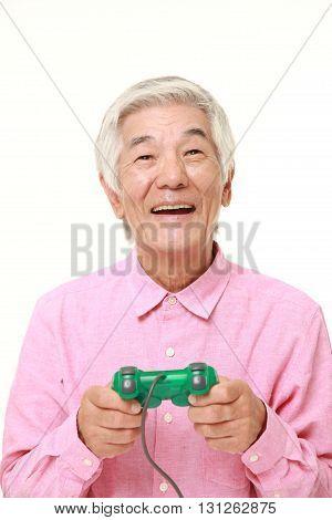 portrait of senior Japanese man enjoying a video game on white background