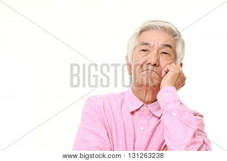 portrait of senior Japanese man worries about something on white background