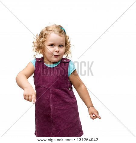 Young little girl with curly hair in purple dress standing and ponting down copy space over isolated white background