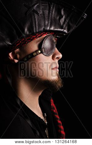 Portrait of a young pirate in profile with leather eyepatch