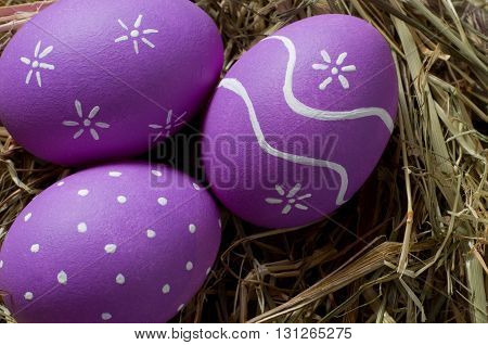 Three colourful easter eggs in a nest